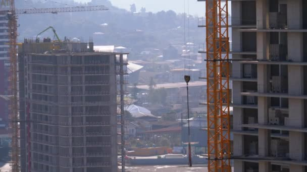 Tower Crane on a Construction Site Lifts a Load at High-rise Building.
