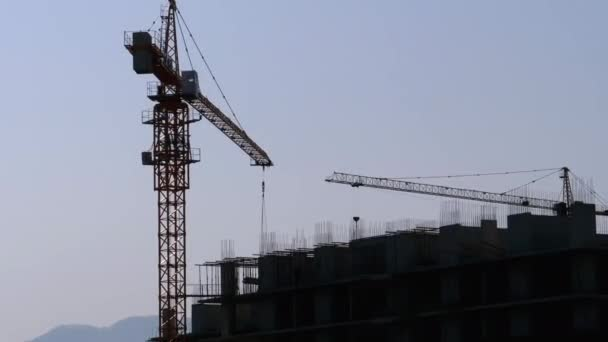 Building Construction. Tower Crane on a Construction Site Lifting Wall Panel