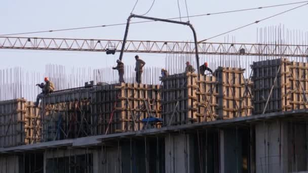 Builders at a Construction Site. Crane on a Construction Site Lifts a Load. Building Construction.