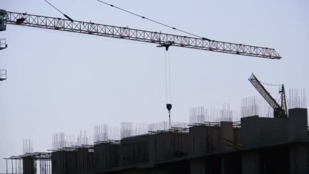 Stavební práce. Tower Crane on a Construction Site Lifting Wall Panel