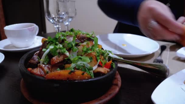 Ojahuri. Smažené vepřové s bramborami a bylinkami v hliněné pánvi v gruzínské restauraci.