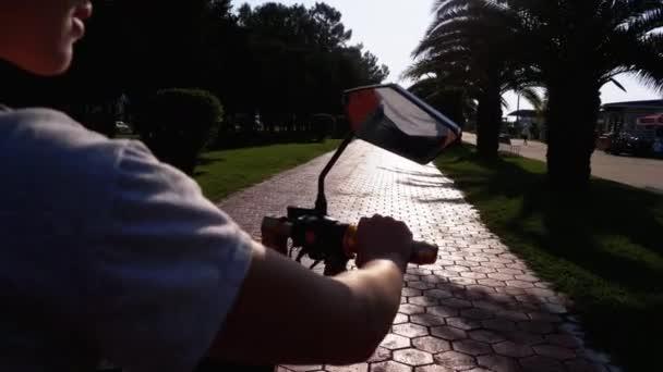 Frau fährt mit Elektrofahrrad auf rotem Radweg mit Palmen in der Kurstadt