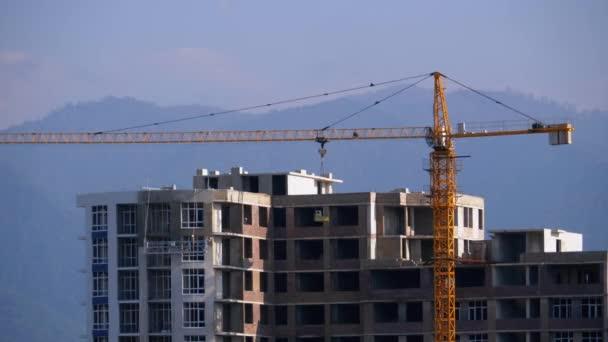 Věžový jeřáb na staveništi zvedá zatížení v budově.