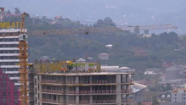 Workers at a Construction Site. Crane on a Construction Site Lifts a Load.