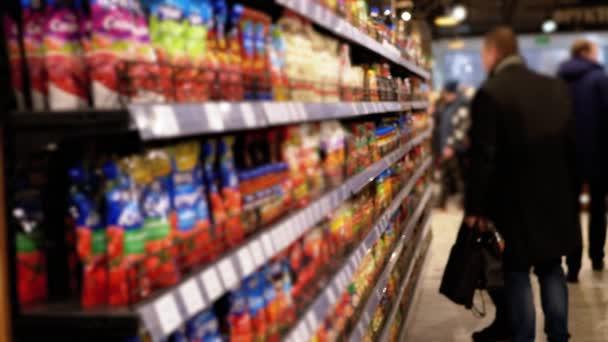 Řádky a police s různým zbožím v supermarketu. Kupující Vyberte si produkt.