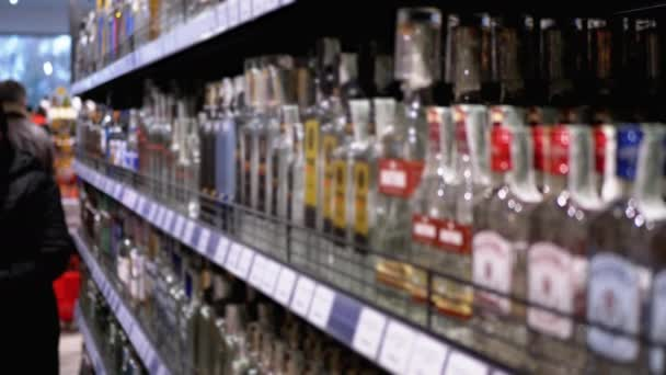 Alkohol eladás a szupermarketben. A palackozott alkohol sorai és polcai a kirakatban