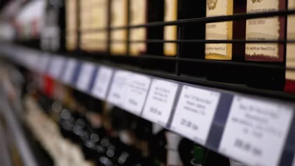 Alkohol eladás a szupermarketben. Sorok és polcok palackozott bor ára Címkék egy bolt ablakán maszat