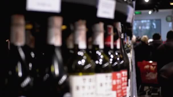 Sorok és polcok palackozott bor ára Címkék egy kirakatban maszat. Alkohol eladás a szupermarketben.