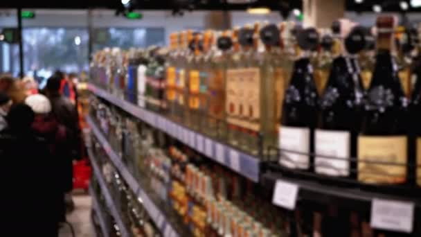 Alkohol eladás a szupermarketben. Sorok és polcok palackozott alkohol árcokkal Címkék egy kirakatban maszat