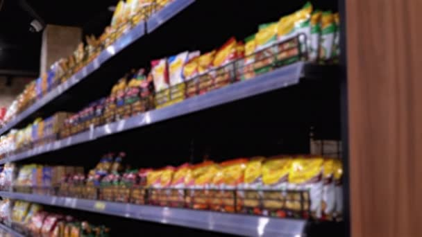 Řádky a police s různými produkty v supermarketu. Kupující Vyberte si produkt.