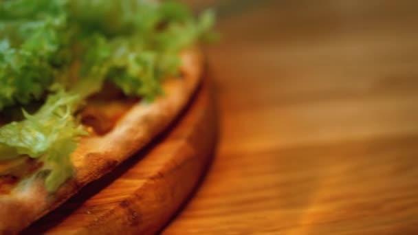 Pizza na dřevěném podnosu na stole v restauraci zblízka. Detailní pohled na ingredience