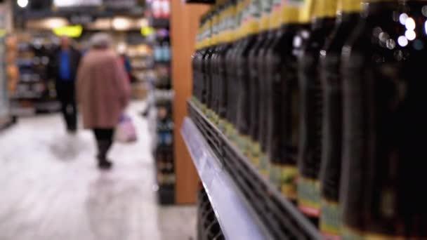 Alkohol eladás a szupermarketben. Palackozott sör sorai és polcai egy kirakaton