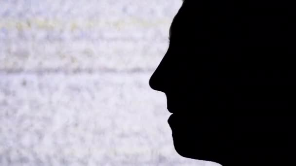 Profile Silhouette of a Male Face on a TV Screen with White Noise and Interference Background.