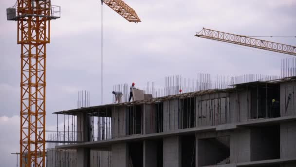 Builders on the Edge of a Skyscraper Under Construction. Workers at a Construction Site.