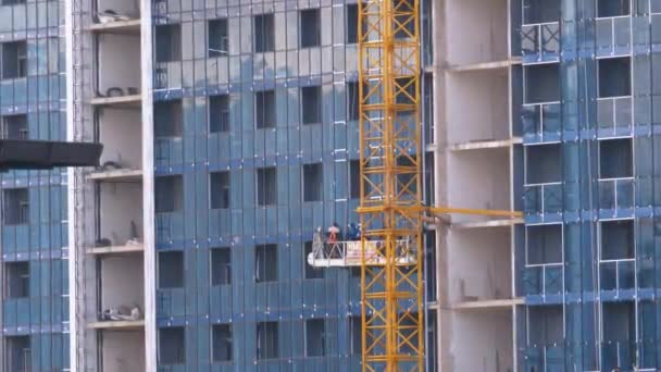 Builders on a construction elevator work at a building under construction with mirrored windows