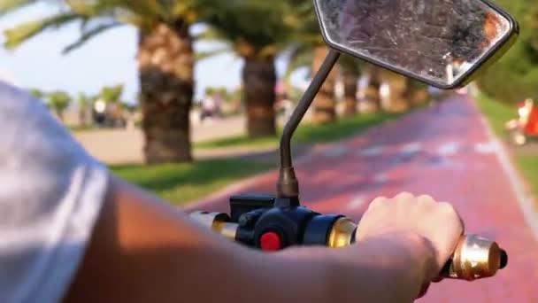 Frau fährt mit Elektroroller auf rotem Radweg mit Palmen in der Kurstadt