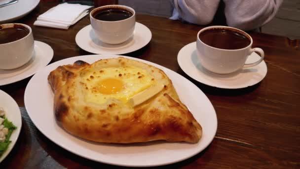 Adjarian Khachapuri az asztalon egy grúz étteremben a saláta, omlett és kávé mellett
