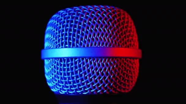 A mikrofon kék és piros háttérvilágítással forog. Dinamikus mikrofon rács pörgetések közelkép