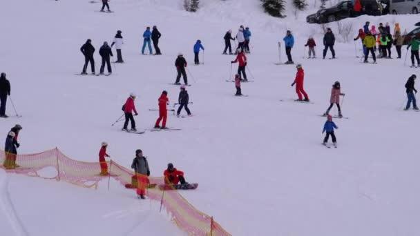 Lyžaři a snowboardisté Jízda na zasněženém svahu v lyžařském středisku ve slunečný den