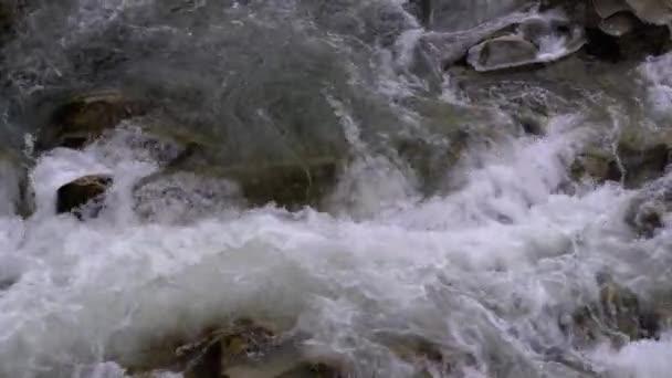 Divoká horská řeka tekoucí kamennými balvany a kamennými peřejemi. Pomalý pohyb