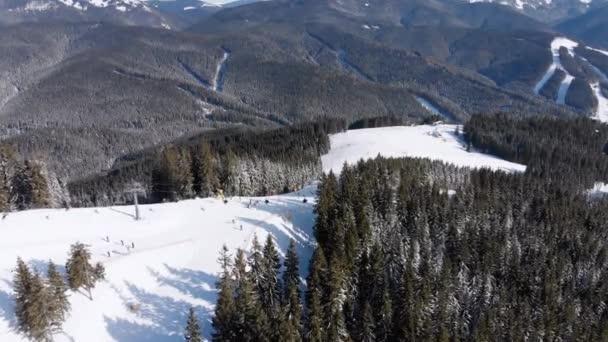 Letecké sjezdovky s lyžaři a vleky na lyžařském středisku. Sněžný horský les