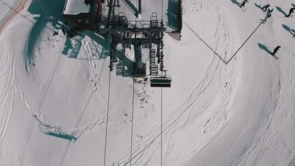 Aerial Top view of Ski Lift for Transportation Skiers on Snowy Ski Slope. Drone Flies over Chair Lift