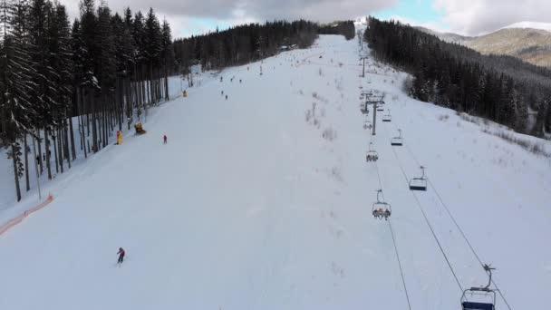 Letecký pohled na sjezdovky s lyžaři a vleky na lyžařském středisku v zimě
