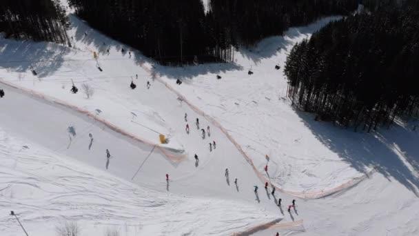 Aerial view Crowd of Skiers Skiing on Peak Ski Slope near Ski Lifts. Ski Resort
