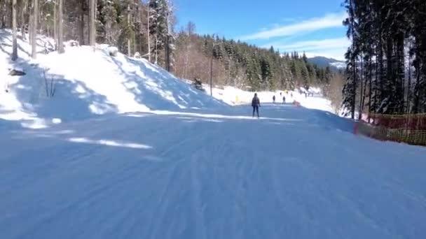 Ego-Blick auf Skifahrer und Snowboarder rutscht auf Skipiste im Skigebiet ab