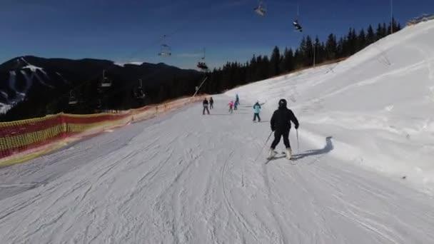 Pohled první osoby Lyžaři a snowboardisté kloužou dolů na sjezdovce v lyžařském středisku