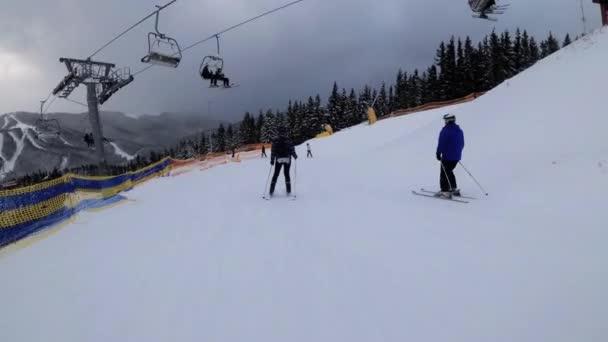 Pohled první osoby na amatérské lyžaře klouzat dolů na sjezdovce v lyžařském středisku