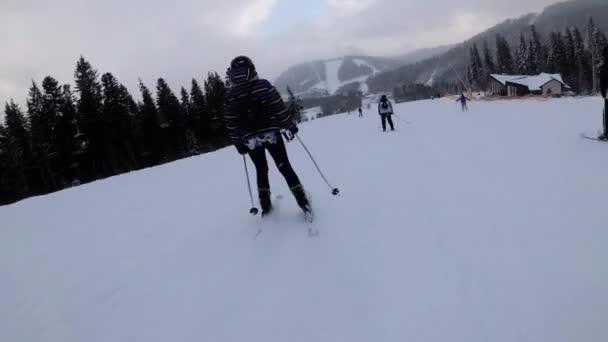 Pohled první osoby na amatérské lyžaře a snowboardisty klouzat dolů na sjezdovce v lyžařském středisku