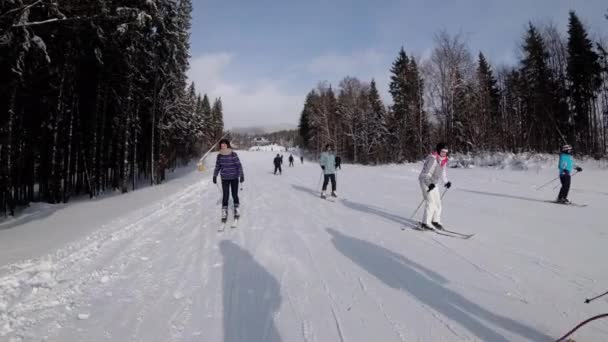 Pohled první osoby na lyžaře a snowboardisty sklouzává dolů na sjezdovce v lyžařském středisku