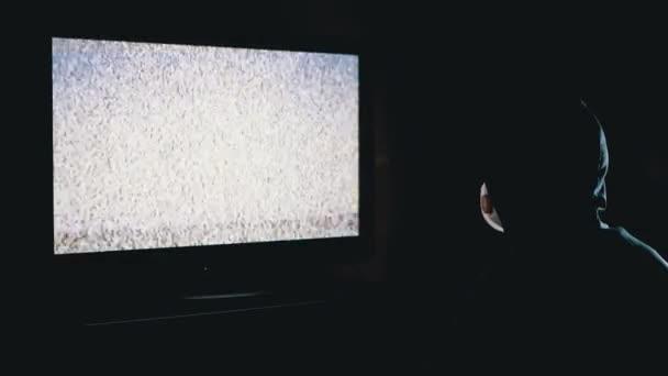 Hamis hírek. Silhouette of Man in Hood és orvosi maszk TV interferencia nézése