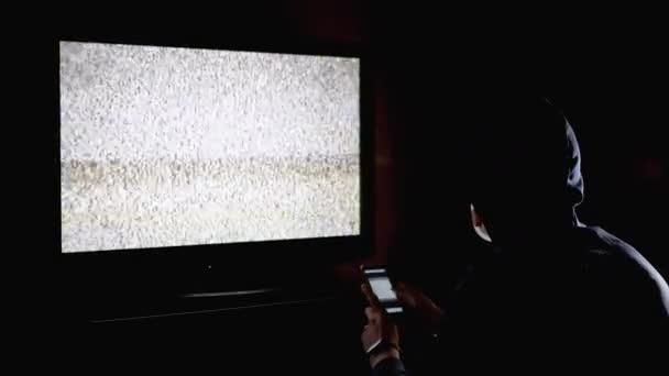 Silhouette Man csuklyás és orvosi maszkos tévénézés interferencia Kezek fel