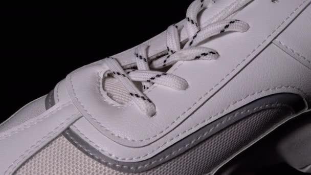 Weißer neuer Sneaker rotiert auf schwarzem Hintergrund. Sport Damenschuhe