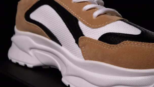 Neuer Sneaker rotiert auf schwarzem Hintergrund. Sport Frau Stilvolle Schuhe