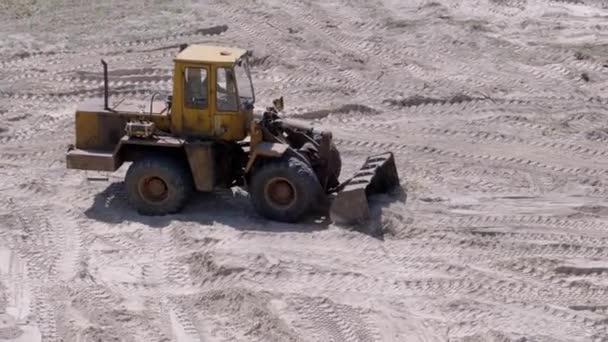 Starý traktor na gumových kolech pohybuje pískem pomocí kbelíku na staveništi
