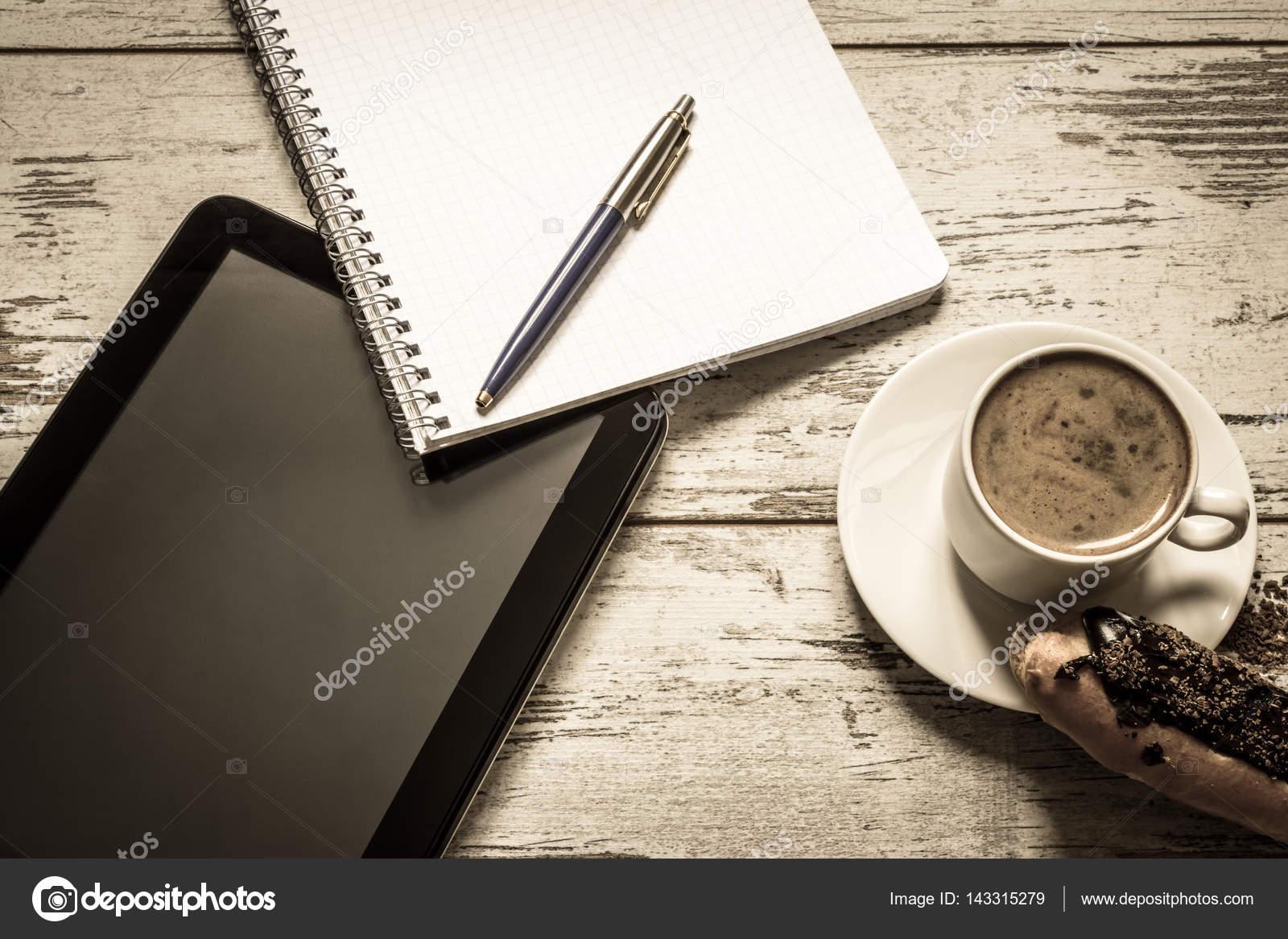 tablet taart Koffie, taart, éclair met chocolade, tablet, notebook en pen close  tablet taart