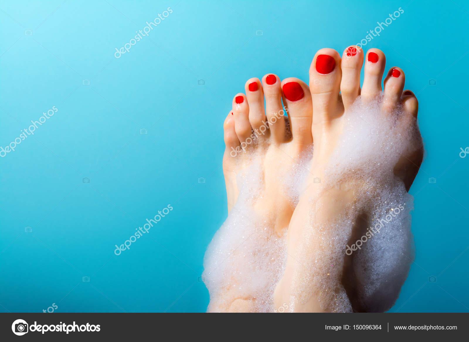 Füße eines jungen Mädchens mit roten Nägeln in einem dicken Schaum ...