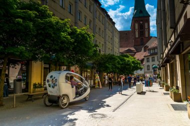 Berlin, Germany -  May 25, 2015: Street in Berlin with a view of the church of St. Nicholas. Located in the historic quarter Nikolaiviertel. Sunny day, blue sky, green blooming trees.