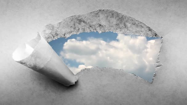 Creative 4k time laps video rychle se pohybující mraky na modré obloze, které jsou viditelné dírou s roztrženými okraji ve starém retro grunge vintage papíru.
