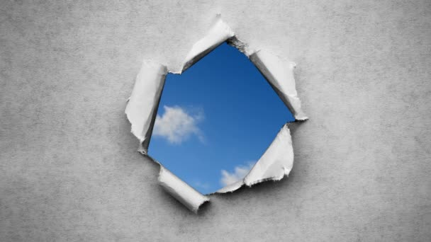 Kreativní 4k čas kola video rychle se pohybující mraky na modré obloze, které jsou viditelné přes kruh otvor s roztrženými okraji ve staré retro grunge vintage papíru.