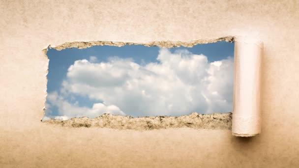 Kreatives 4k-Zeitraffer-Video von sich schnell bewegenden Wolken am blauen Himmel, die durch ein Loch mit abgerissenen Kanten in altem Retro-Grunge-Vintage-Papier sichtbar sind.