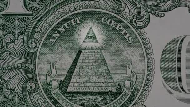 Creative 4k video of details of a 1 american dollar banknote macro closeup with a pyramid and the effect of a glowing mason eye on top. Pyramid close-up on a banknote of 1 US dollars.