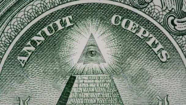Creative 4k parallax video of details of 1 American dollar banknote with a rotating eye at the top of the pyramid. Macro view.