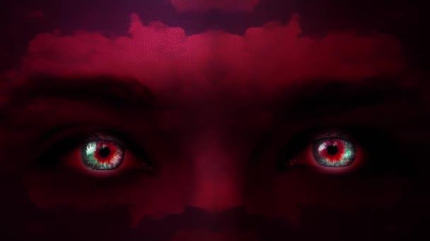 Kreativní 4k video mystické ženy tvář červené barvy zblízka s barevnými očima a vzory pohybujících se mraků na její tváři. Záhadný pohled. Zářící oči ve tmě.