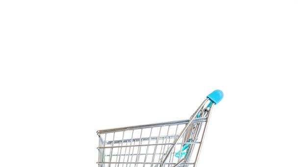Nákupní košík se pohybuje rychle ze strany na stranu a rychle se plní zeleninou a ovocem. Hora čerstvé zeleniny a ovoce v přeplněném vozíku. Spotřebitelský, prodejní a nákupní koncept.