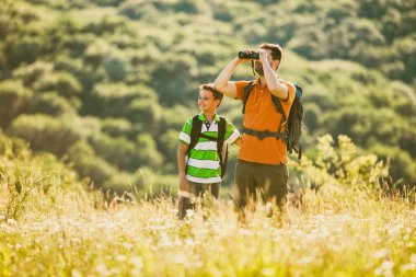 Father and son are hiking in nature in summer. They are using binoculars.