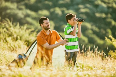 Father and son are camping and exploring nature.